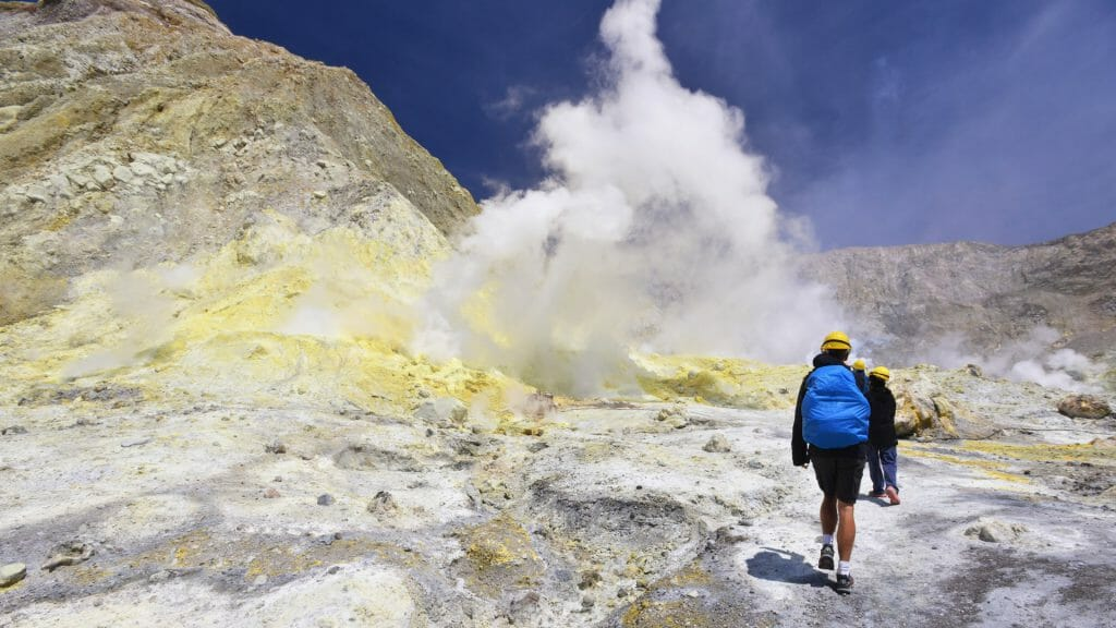 Back of a man with blue rucksac walking on volcanic landscape of white and yellow with smoke rising.