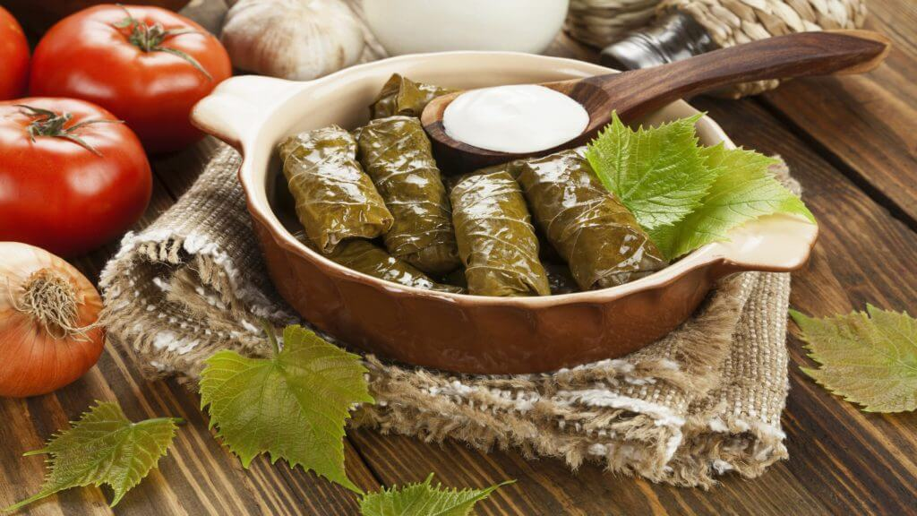 Dolma from grape leaves and minced on the wooden table, Greece