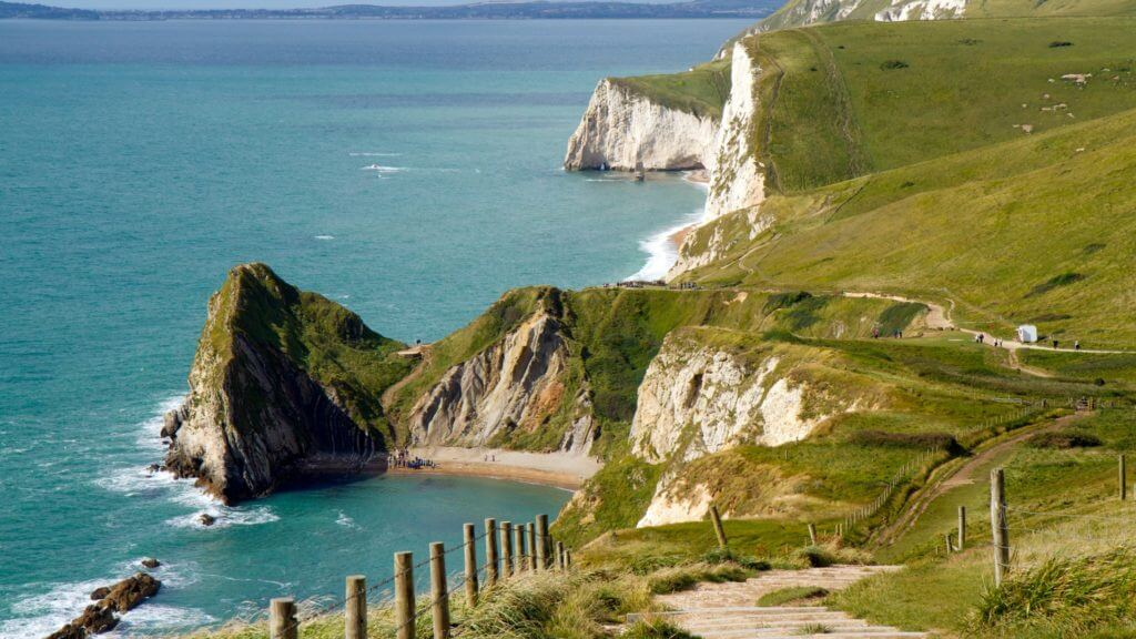Footpath at the edge of a cliff overlooking blue ocean. South West Coast Path in Dorset