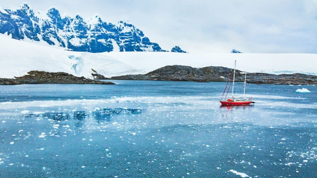 A small red yacht sailing on blue ocean against a backdrop of snow covered mountains in Antarctica